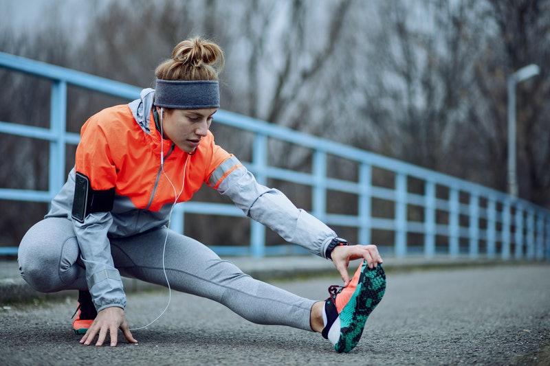 Young athletic woman doing stretching exercises and preparing for sports training during cold weather.