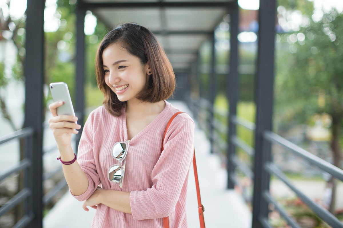 Asia woman using with smart phone in the street in a sunny summer day