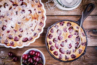Clafoutis cherry pie on rustic wooden background