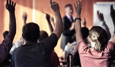 Raised hands and arms of large group of people in class room, audience voting in professional educat...