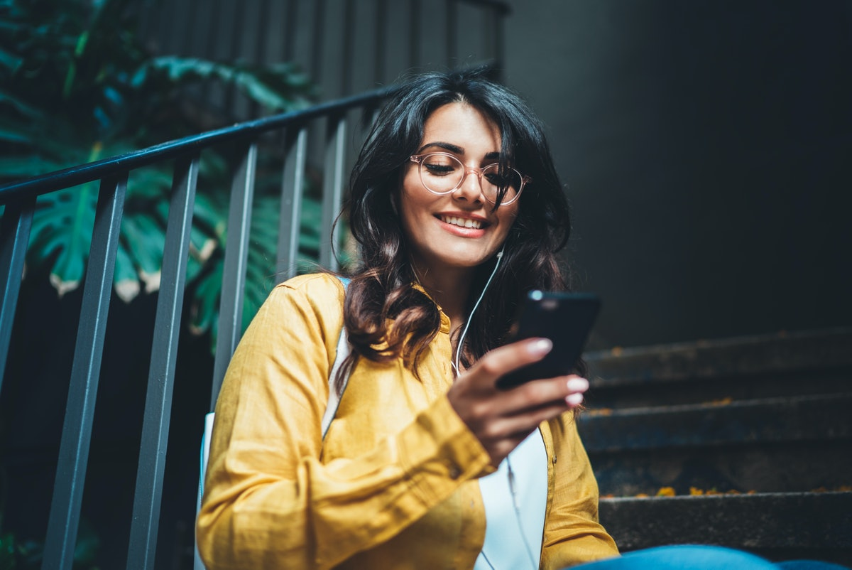 A trendy brunette woman smiles while sitting on the steps of her apartment and texting.