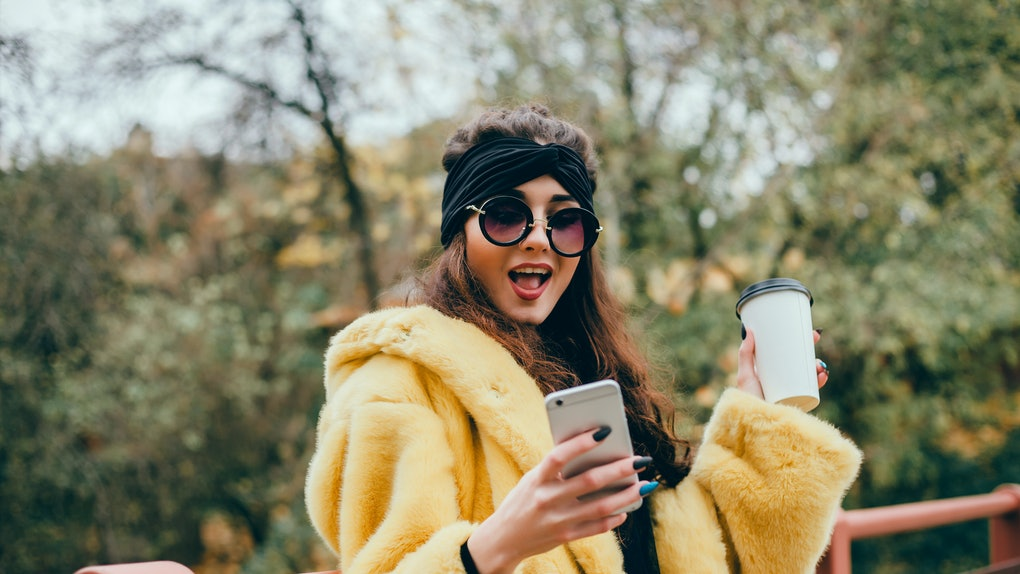 A woman in a yellow faux fur coat, black sunglasses, and a black headband looks at her phone and holds up a to-go coffee cup while standing on a bridge.