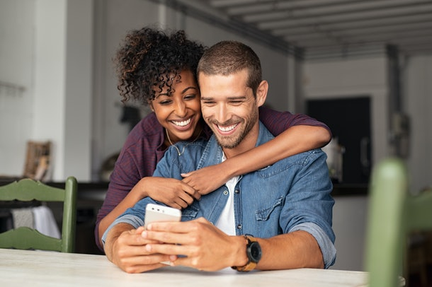 A happy young couple looks at a cell phone.