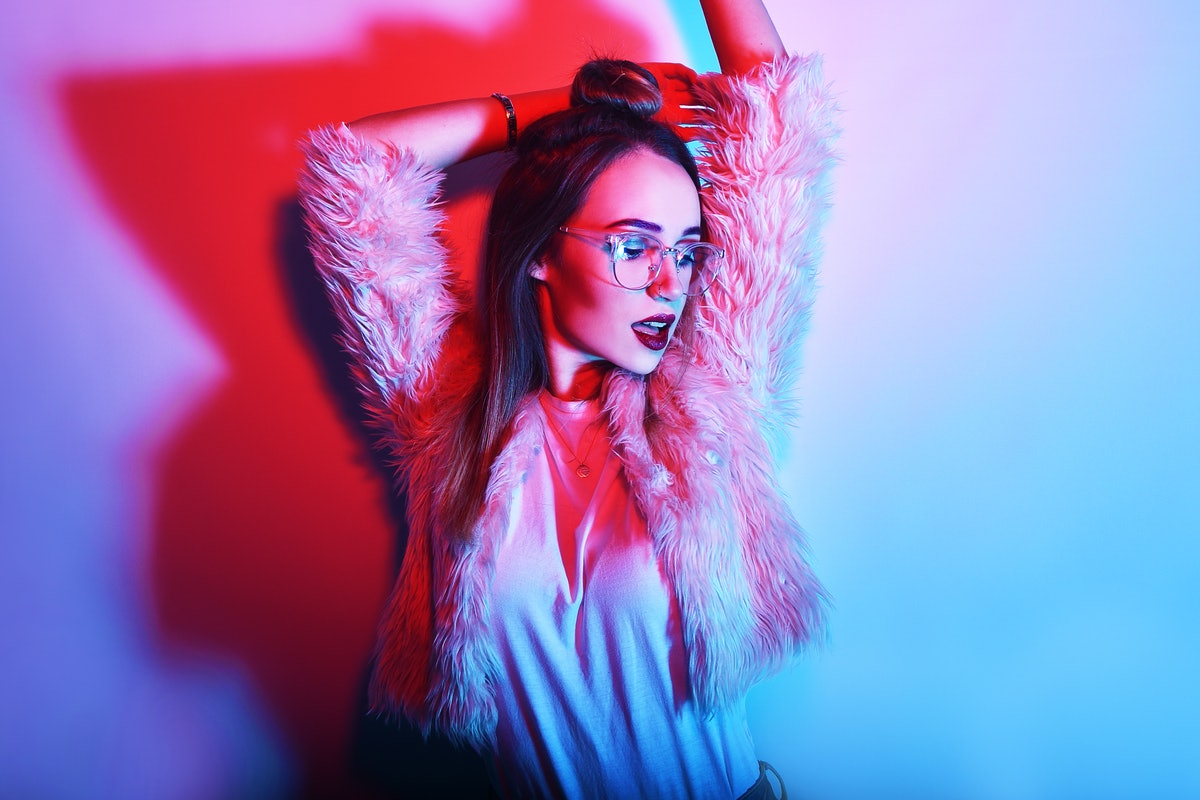 Fashion portrait of young elegant girl in glasses. Colored background, studio shot. Beautiful brunette woman. hipster girl dancing in neon. Woman with stylish hair and red lips.