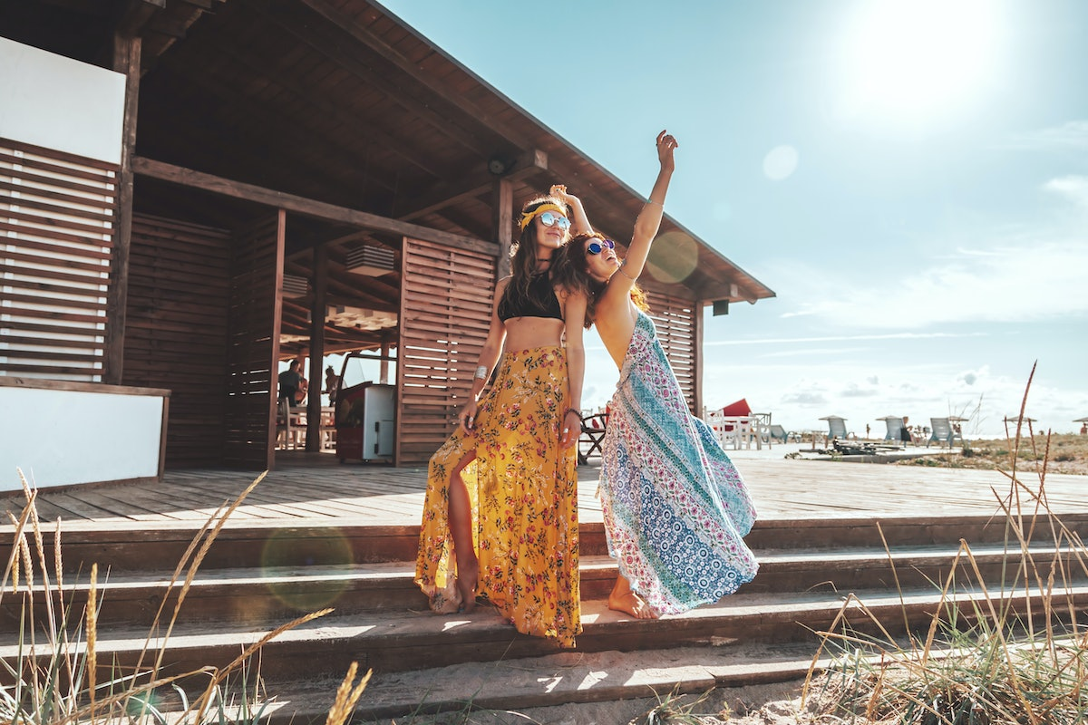 Two female friends wearing sunglasses and maxi skirts smile and pose on the steps of a beach shack on a sunny day.