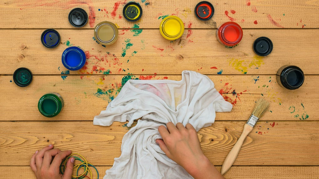The girl rolls up a white t-shirt for painting in the style of tie dye. Staining fabric in tie dye style.
