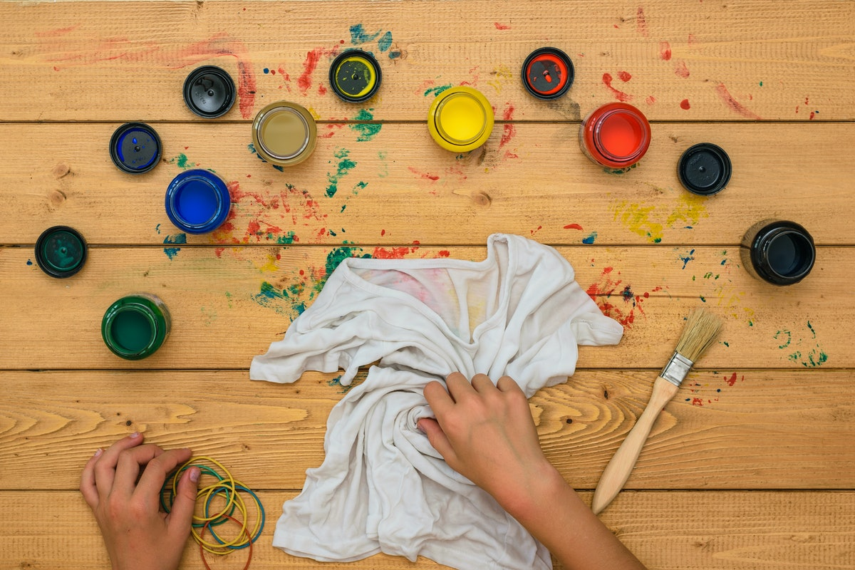 The girl rolls up a white t-shirt for painting in the style of tie dye. Staining fabric in tie dye s...