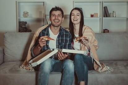 The happy couple eating a pizza and watch a movie on the sofa