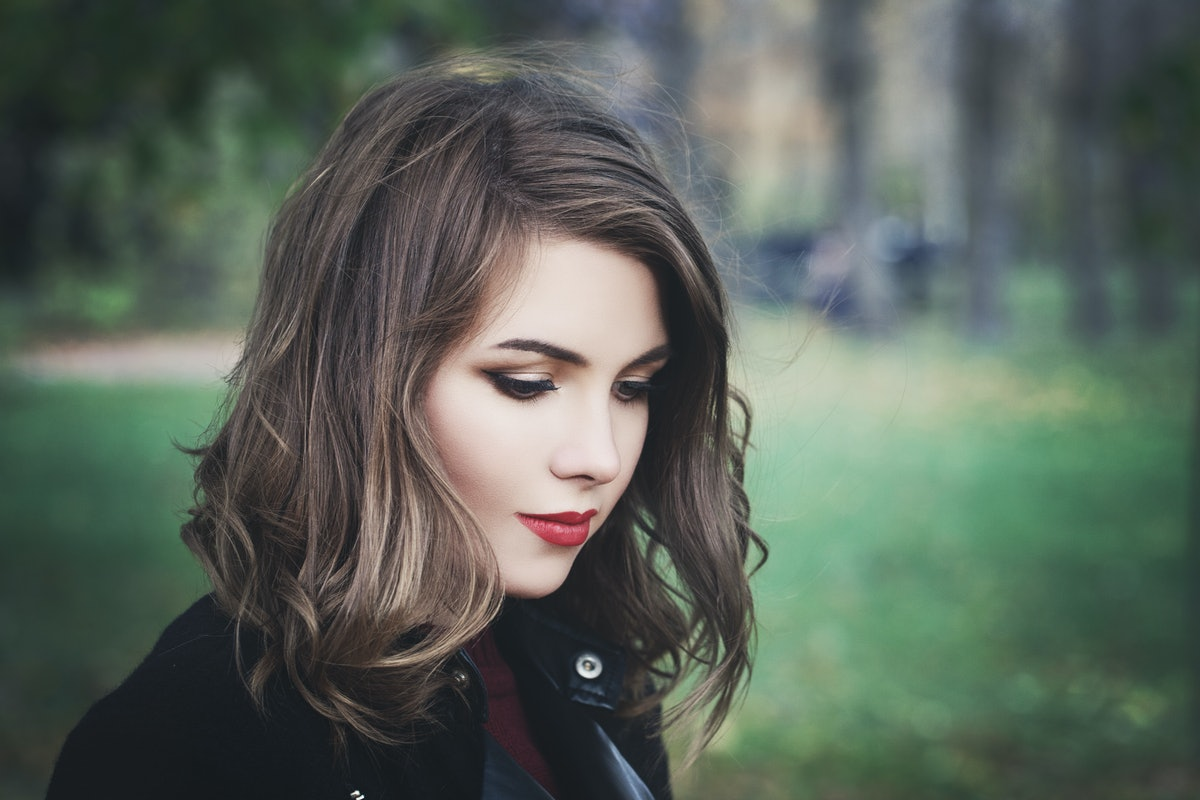 Lovely Girl in the Park. Pretty Woman with Long Bob Hairstyle