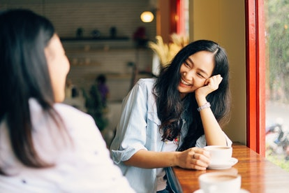 Two Asian woman chatting and drinking coffee at cafe.