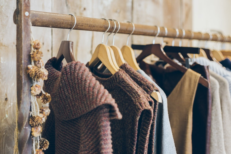 Fashion trend concept. Warm winter ladies clothes collection with wool dresses and knitted jumpers on wooden hangers.