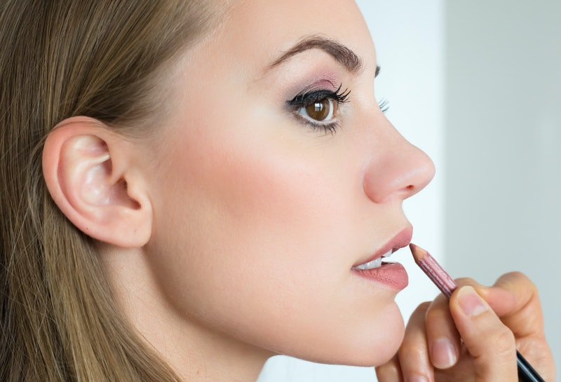 Applying lip liner on young beautiful woman