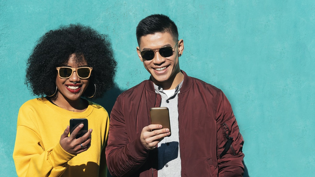 Two happy friends text on their phones in front of a turquoise wall on a sunny day.