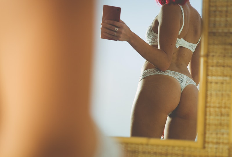 Woman taking selfie with mirror reflection in lingerie. People losing their jobs due to the coronavirus pandemic are turning to camming, but veteran sex workers say that's hurting their business.