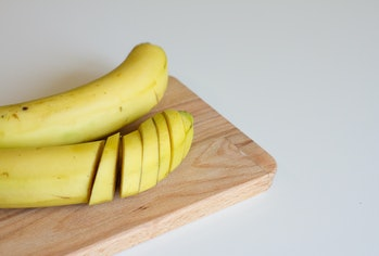 ripe yellow banana on a wooden Board on a white background. there are two bananas on the table. the banana slices. sliced banana. fresh fruit. space for text. the view from the top.