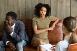 African frustrated wife talking to psychologist sitting on couch with husband, black unhappy woman sharing marital problems with counselor, family marriage therapy session, couple counseling concept