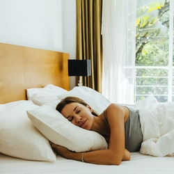 Woman sleeping on bed in luxury hotel room in the morning infront of big window. Chilling well on co...