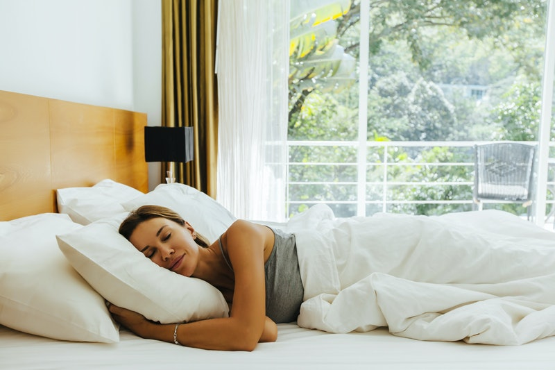 Woman sleeping on bed in luxury hotel room in the morning infront of big window. Chilling well on comfy matress and pillows.