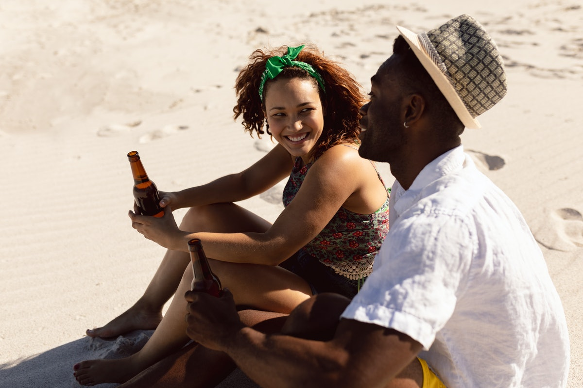 A happy couple chats and holds their beer bottles while sitting on a beach on a sunny day.