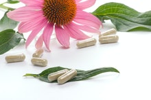 Closeup of Echinacea extract pills and fresh Echinacea flower leaves best suited for alternative med...