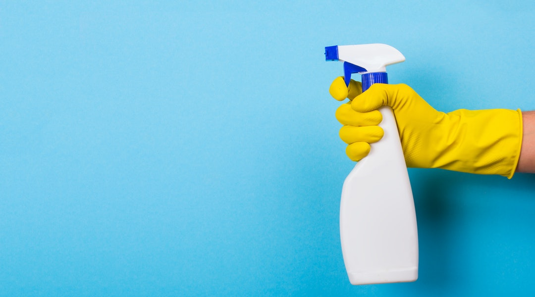 A hand in a yellow glove holds a spray of cleaning fluid on a blue background. Copy space