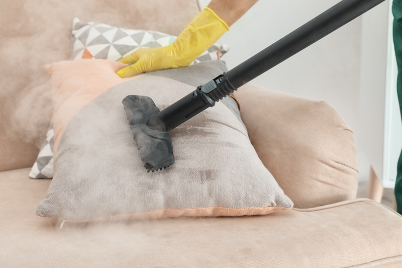 Janitor removing dirt from sofa cushion with steam cleaner, closeup