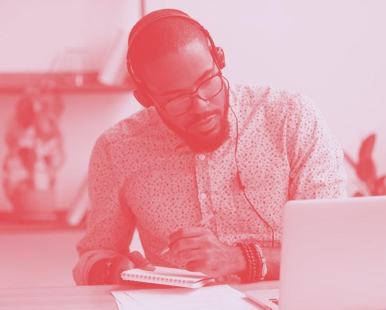 Focused african business man in headphones writing notes in notebook watching webinar video course, ...
