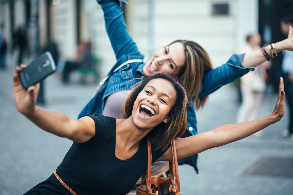 Two women make a silly pose outside while taking a selfie.