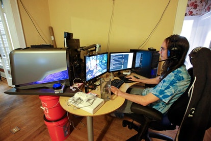 Brett Borden sits at a desk with multiple computers and video screens where he plays video games for...