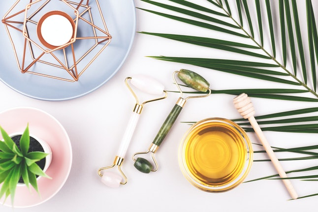 Beauty composition with trendy pink and green jade rollers, honey and candle on grey background. Selfcare, home spa and relaxation concept. Flat lay, top view.