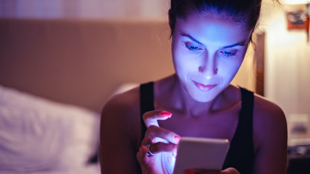 Girl looking at mobile phone in the dimmed bedroom