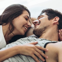 Young couple lying in bed together. Romantic couple in love looking at each other and smiling.