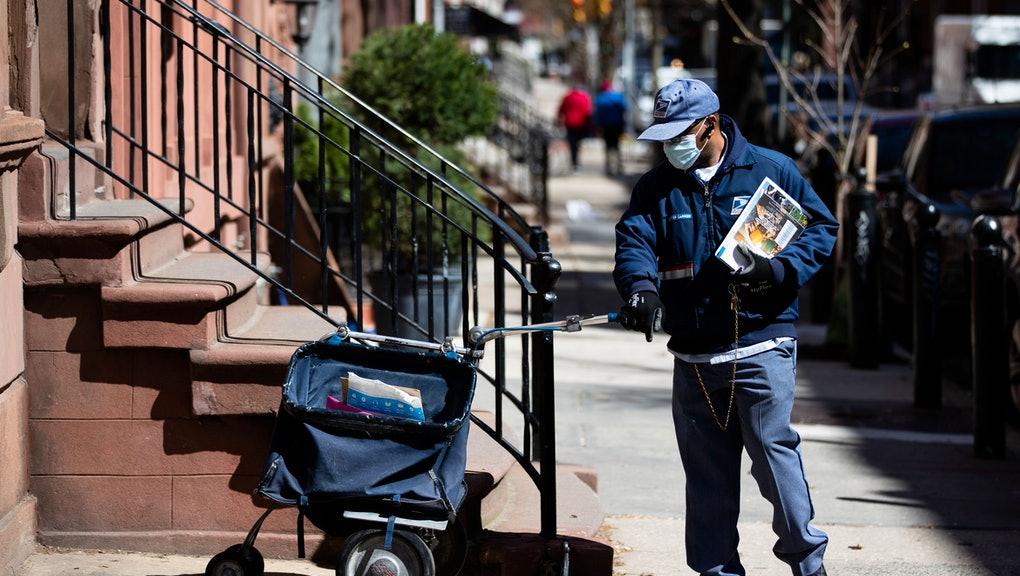 United States Postal worker makes a delivery with gloves and a mask in Philadelphia, . The U.S. Post...