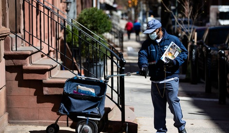 United States Postal worker makes a delivery with gloves and a mask in Philadelphia, . The U.S. Postal Service is keeping post offices open but ensuring customers stay at least 6 feet (2 meters) apart. The agency said it is following guidance from public health experts, although there is no indication that the new coronavirus COVID-19 is being spread through the mail