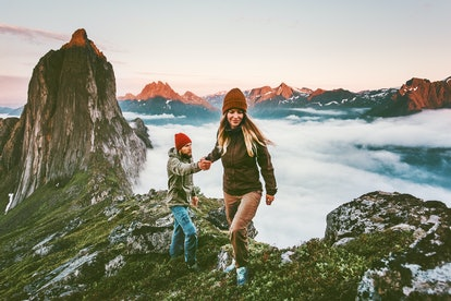 Woman hiking atop a tall mountain