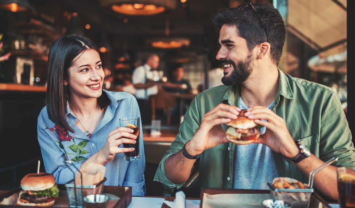 Happy loving couple enjoying breakfast in a cafe. Love, dating, food, lifestyle concept
