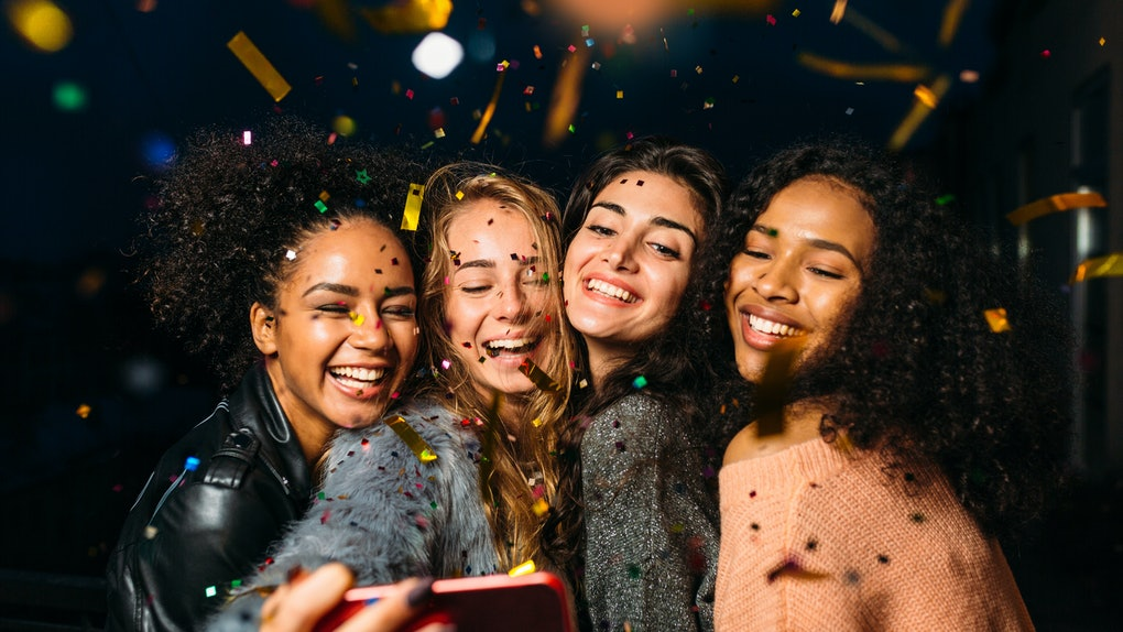 A group of friends all smile for a selfie picture as colorful confetti falls all around them.