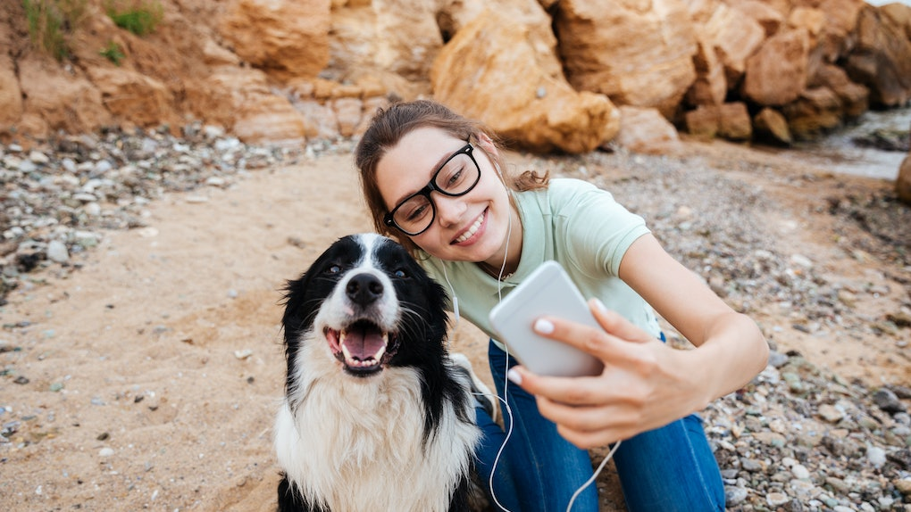 A woman wearing glasses takes a selfie with her dog while they're outside on a walk.