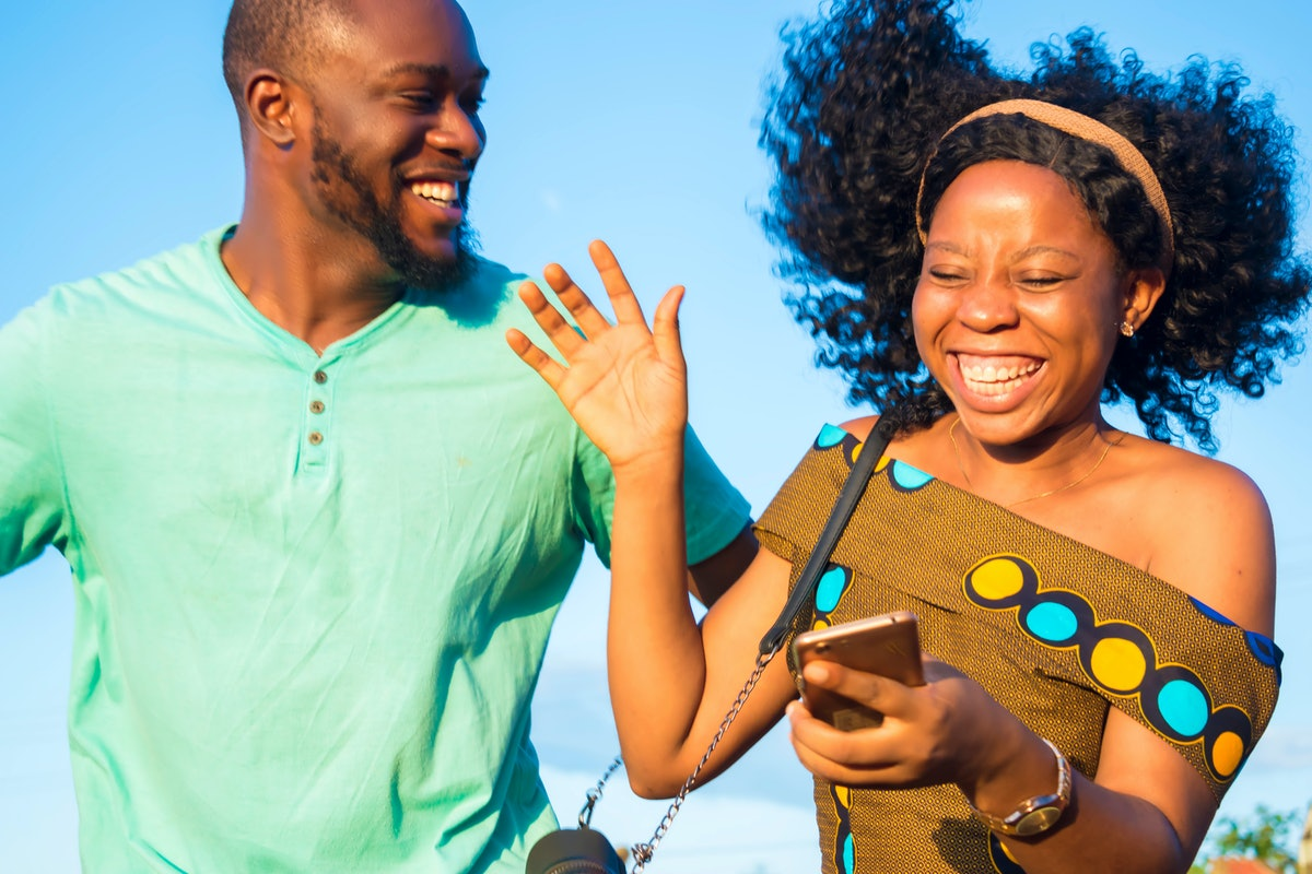 A happy couple jumps in the air together, while holding their smart phone.