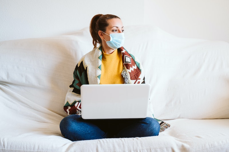 young woman working on laptop at home, sitting on the couch, wearing protective mask. Stay home concept during coronavirus covid-2019