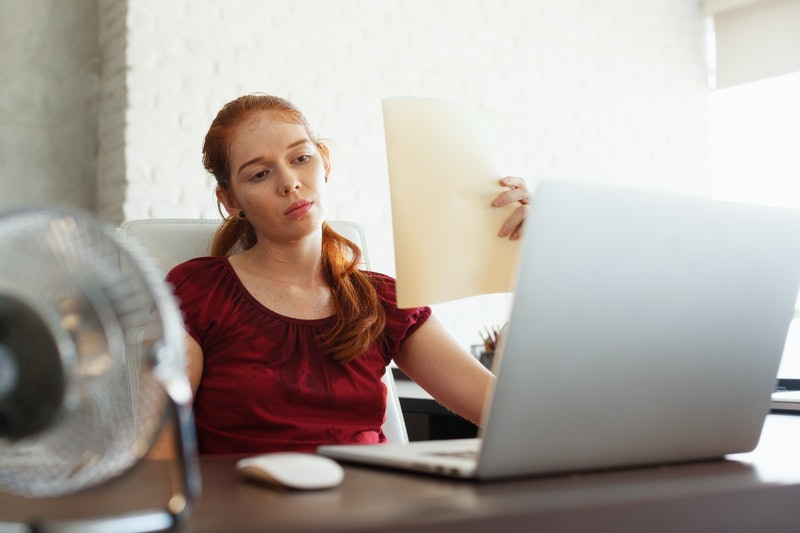 Portrait of young redhead woman working with computer laptop in office at summer during heatwave. The temperature is hot and the hair conditioner is broken. The girl sweats and feels exhausted