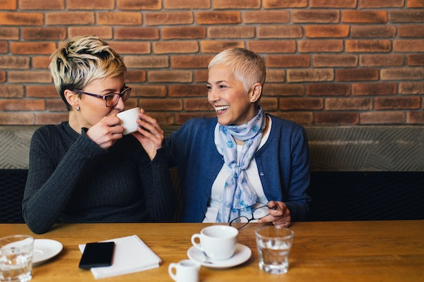 A mom and daughter smile and enjoy coffee in a café.