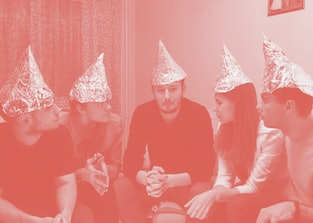 Group of people with foil on their heads discussing conspiracy theories. Friends with foil on their heads. You know, so they can't read your mind
