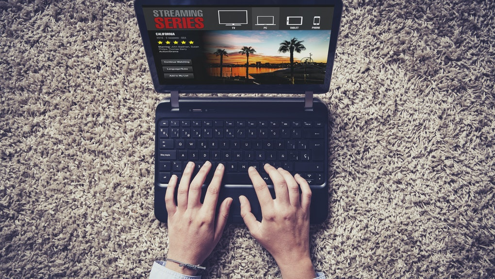 Streaming tv series website in a laptop computer. Hands typing on the keyboard.