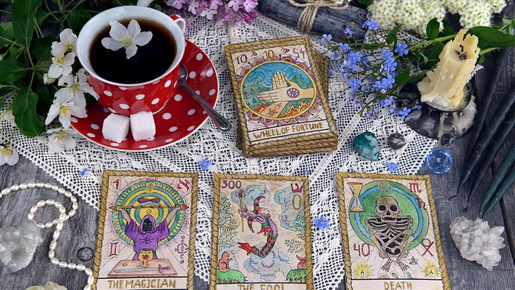 Tarot cards with cup of tea, flowers and black candles on planks. Occult, esoteric and divination still life. Halloween background with vintage objects and magic ritual