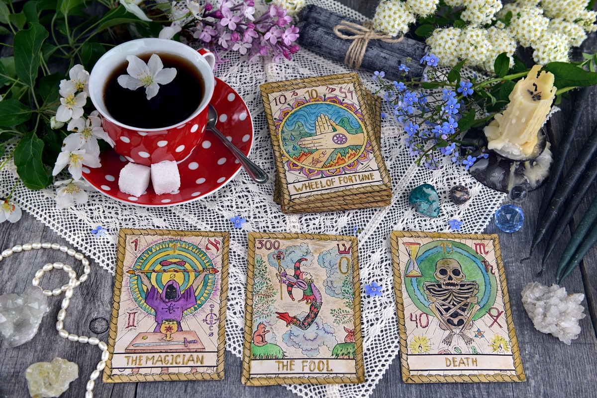 Tarot cards with cup of tea, flowers and black candles on planks. Occult, esoteric and divination st...