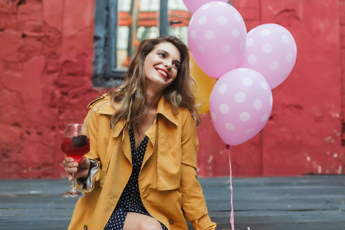 A woman wearing a yellow jacket, holds a glass of sangria and some pink balloons, while sitting outside.