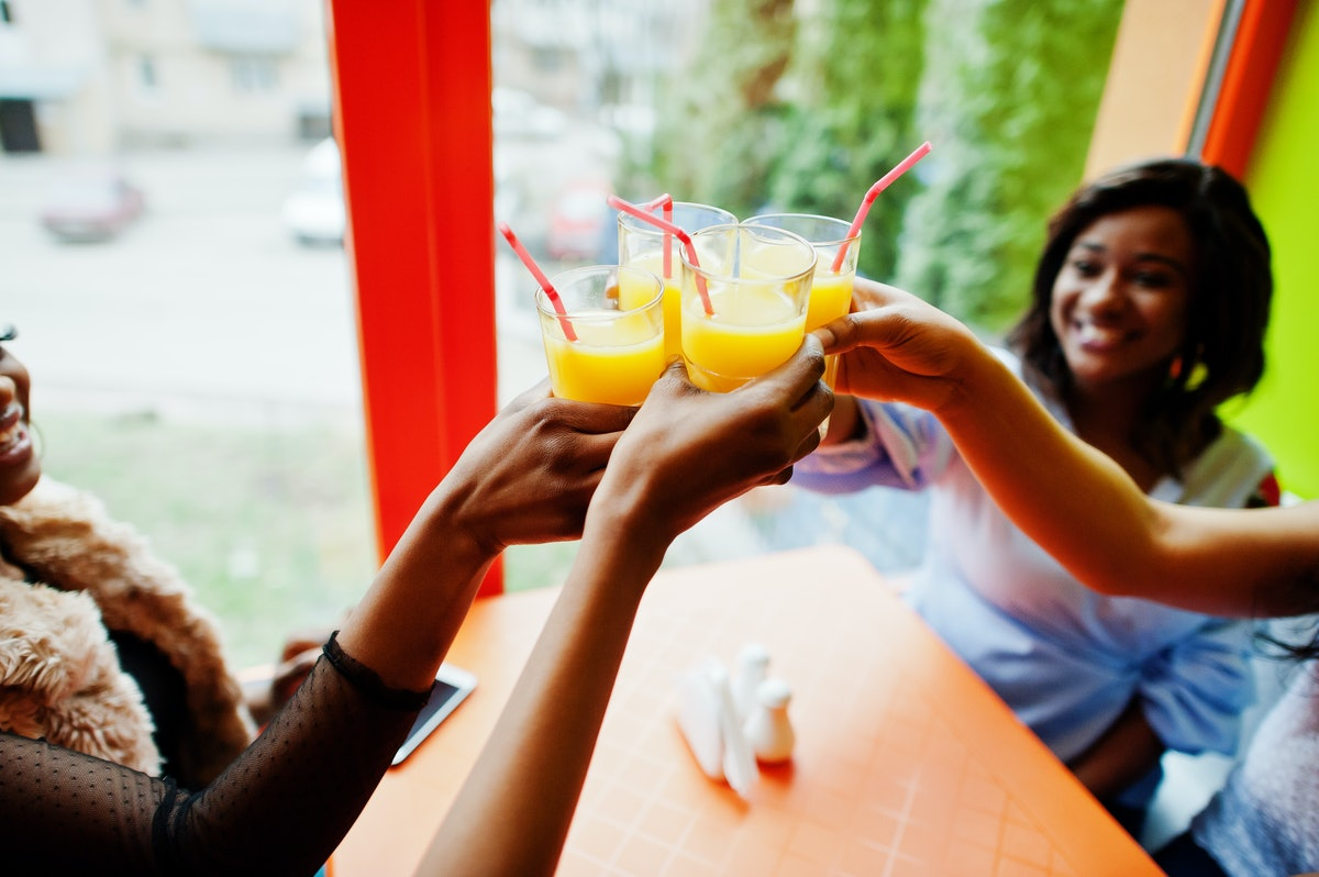 A group of friends cheers their orange juice glasses with pink straws at a table.