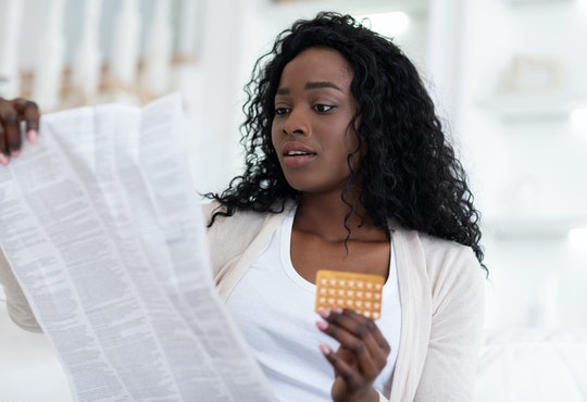 Shocked african american woman reading leaflet before taking contraceptive pills, sitting on couch at home