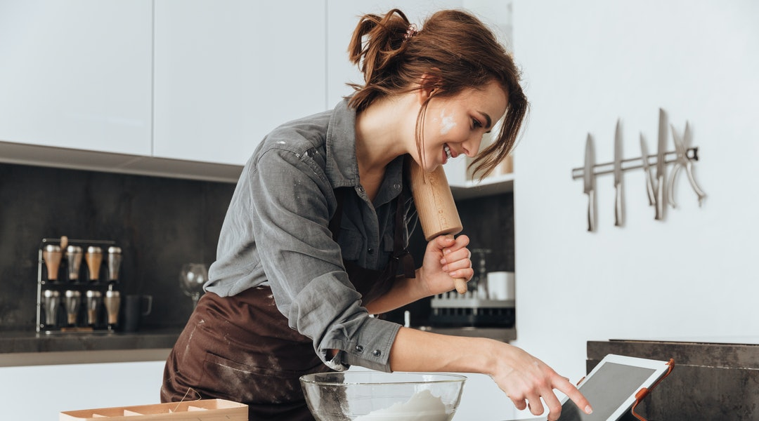 Image of young pretty lady standing in kitchen and cooking the dough. Looking at tablet computer.